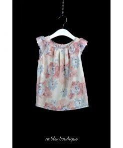 Blusa fantasia fantasia di fiori slavati e fondo rosa pallido, maniche corte con leggero volant. Bottoni sul retro tono su tono.