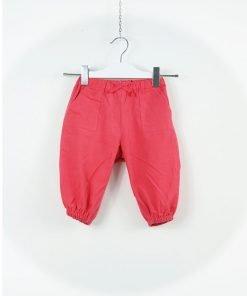 Pantalone in morbido velluto a costine color fragola, elastico in vita con applicazione di un fiocchetto tono su tono, tasche laterali, elastico sul fondo.
