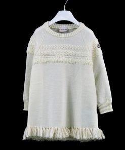 Vestito color panna girocollo di Moncler con frange tono su tono sul fondo e piccoli fili nel core oro, ricamo frontale che continua sulle maniche.