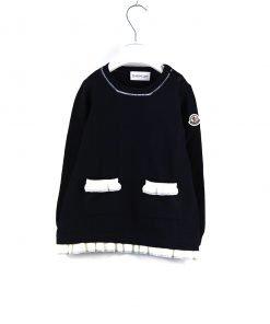 Vestito in lana blu scuro a maniche lunghe di Moncler, bottoncini sulla spalla, due tasche in color avorio e fondo del vestito sempre in panna con volant.