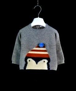 Maglione girocollo grigio con disegno di pinguino con cappello e pom pom blu. Due bottoncini sul retro per agevolare l'apertura.