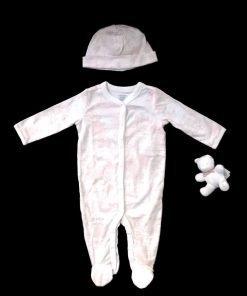 Questo set è composto da una tutina in morbido cotone con un delicato disegno rosa pallido sul fondo bianco, un berretto coordinato e un grazioso orsetto
