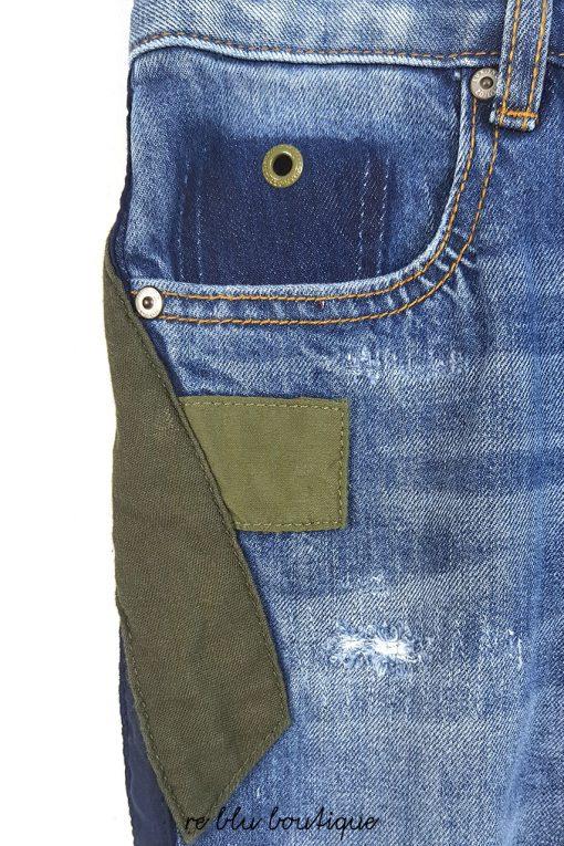 Jeans skinny bluette con toppe verdi militare e blu, modello skinny dritto. Il jeans è slavato con leggeri e piccoli strappi