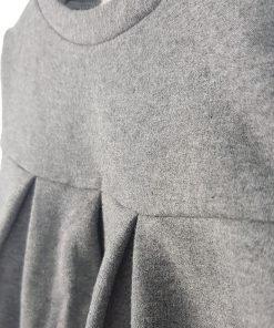 Felpa girocollo grigia melange con dettaglio di bordino bianco ottico, scritta stampata sul retro. Modello a campana, arricciatura frontale