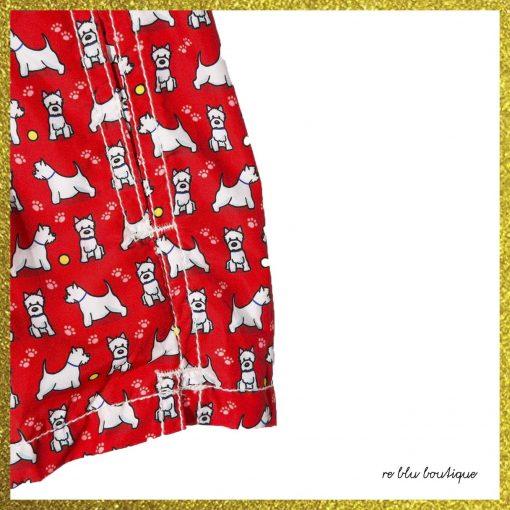 Costume Saint Barth modello boxer rosso con stampa di piccoli cani bianchi su tutta la superfice, elastico in vita con coulisse, tasche laterali, spacchi laterali e tasca posteriore con pattina.