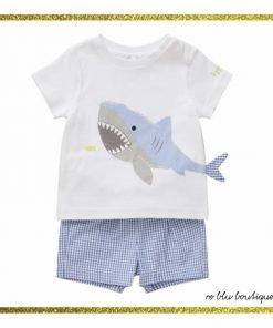 Completo due pezzi da neonato Il Gufo composto da t-shirt in cotone bianco e bermuda. Stampa squalo e applicazioni di tessuto sulla pinna. Parte sotto in seersucker quadrettato azzurro.