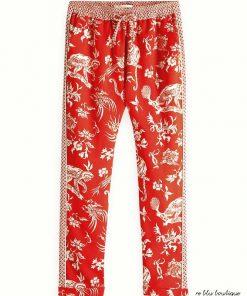 Pantaloni Scotch R'Belle stampati con diverse fantasie su un fondale rosso acceso, vita elasticizzata con coulisse. Tasche laterali e caviglie elasticizzate, caviglie con bordi elasticizzati