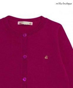 Un bel cardigan in lana merinos Bonpoint per scaldare cuori e vestiti. Il bel colore rosa fucsia di questa maglia abbottonata sopra l'intera altezza è la sua vera forza.È associato a vestiti neri per aumentare il tutto.